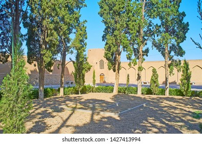 KASHAN, IRAN - OCTOBER 23, 2017: The shady Fin garden is surrounded by tall medieval brick wall with towers on its corners, on October 23 in Kashan