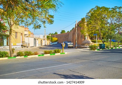 KASHAN, IRAN - OCTOBER 23, 2017: The street of old town with line of living buildings, greenery of public Mellat park and ruins of adobe fortress wall of Ghal'eh Jalali, on October 23 in Kashan