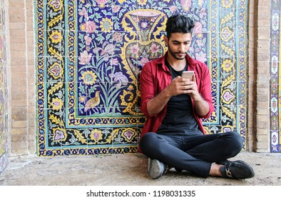 KASHAN, IRAN- SEPTEMBER 23, 2018: A young Iranian man sits near a wall with tiles school and mosque Agha Bozorg in Kashan, Iran