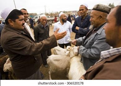 KASHGAR, CHINA - 23 AUGUST 2012 - Men barter for sheep at the weekly Kashgar livestock market, Xinjiang province