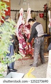 KASHGAR, CHINA - MAY 10, 2018: An unidentified Muslim merchant selling beef to customer at his shop on the street of Kashgar Ancient Town in Xinjiang, China.