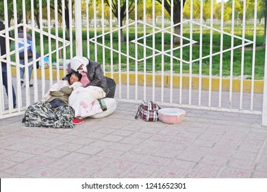 KASHGAR, CHINA - MAY 7, 2018: Unidentified poor Uyghur Chinese couple sitting and sleeping in front of Kashgar railway station waiting for gate open in the morning, Xinjiang, Western China.
