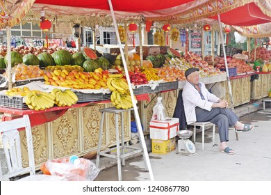 KASHGAR, CHINA - MAY 9, 2018: An Uyghur man is the owner of a fruit stall in street food market everyday at inner Kashgar old town in the Xinjiang Uyghur Autonomous Region, Western China.