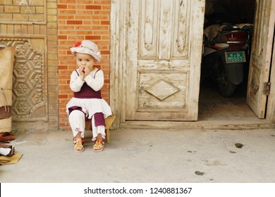 KASHGAR, CHINA - MAY 9, 2018: An unidentified cute Muslim young little girl in white and red dress sitting in front of her house in renovated building zone of Kashgar Ancient Town in Xinjiang, China.