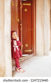 KASHGAR, CHINA - MAY 9, 2018: An unidentified cute Muslim young little girl in red dress standing in front of her house in renovated building zone of Kashgar Ancient Town in Xinjiang, China.