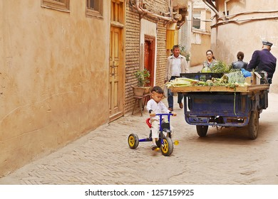 KASHGAR, CHINA - MAY 9, 2018: A street vendor with some housing residents walking in narrow alley of renovated building zone in Kashgar Ancient Town, the Xinjiang Uyghur Autonomous Region, China.