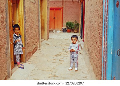 KASHGAR, CHINA - MAY 9, 2018: Unidentified two cute Muslim Uyghur young boy and girl standing on the street in front of their house in renovated building zone of Kashgar old town in Xinjiang, China.