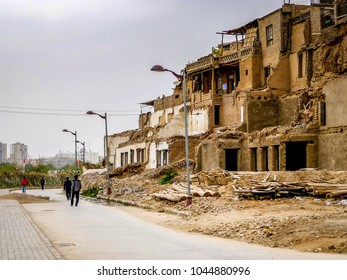 KASHGAR, CHINA - Oct 2011: Pedestrians walk past the crumbling mud brick old town of Kashgar in the Xinjiang Uygur Autonomous Region of western China