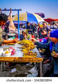KASHGAR, CHINA - Oct 2011: A Uyghur man serves food to a group of people at the Yopurga weekly market near Kashgar in the Xinjiang Uygur Autonomous Region in western China