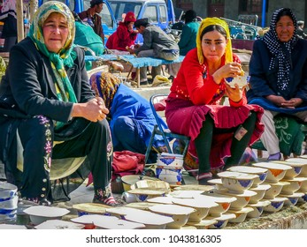 KASHGAR, CHINA - Oct 2011: Uyghur women sell bowls of yoghurt at the weekly Yopurga market near Kashgar in the Xinjiang Uygur Autonomous Region in western China