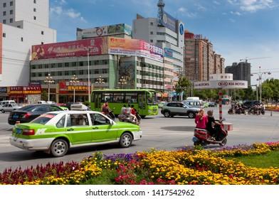 Kashgar, Xinjiang, China - August 14, 2012: Street scene in the city of Kashgar with vehicles at a roundabout, Xinjiang, China