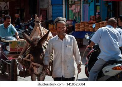 Kashgar, Xinjiang, China - August 14, 2012: Uyghur man with a donkey at a street market in the city of Kashgar, Xinjiang, China