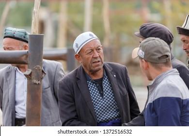 KASHGAR, XINJIANG / CHINA - October 1, 2017: Uyghur men having a conversation at Kashgar Animal Market. They probably negotiate the price for some animals, like lambs, sheeps or yaks.
