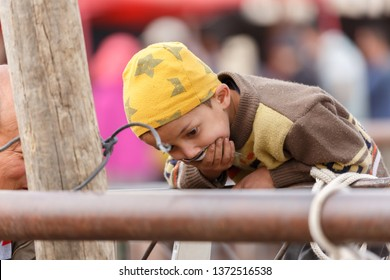 KASHGAR, XINJIANG / CHINA - October 1, 2017: Uyghur boy with hand before mouth is watching animals at Kashgar Animal Market
