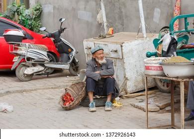 KASHGAR, XINJIANG / CHINA - October 1, 2017: Elderly Uyghur man with a beard selling pomgranates at a bazaar in Kashgar. The man is wearing a doppa (traditional hat).