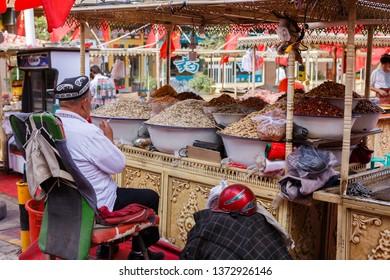 KASHGAR, XINJIANG / CHINA - October 1, 2017: A look behind a market stall at a bazaar at Kashgar Old Town. The shopkeeper is waiting for customers buying his raisins and nuts.