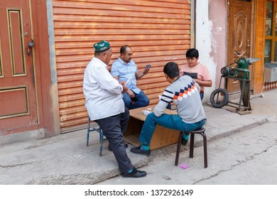 KASHGAR, XINJIANG / CHINA - October 1, 2017: Four Uyghur men playing a card game. The photo was captured in the streets of Kashgar Old Town.