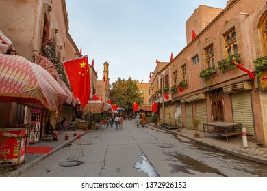 KASHGAR, XINJIANG / CHINA - October 1, 2017: View on a street in Kashgar Old Town. People strolling, shops on the left and right side of the street. Chinese flags due to Chinese National Holiday.