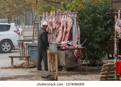 KASHGAR, XINJIANG / CHINA - October 1, 2017: Butcher preparing meat - probably lamb - captured at Kashgar Animal Market.