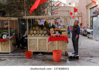 KASHGAR, XINJIANG / CHINA - October 1, 2017: Markt stall in Kashgar Old Town with water and honey melons on display for sale. The shopkeeper is probably looking for customers.