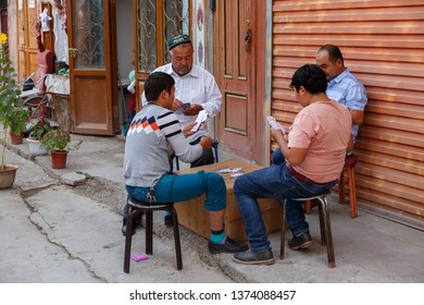 KASHGAR, XINJIANG / CHINA - October 1, 2017: Four Uyghur men playing cards on a street in Kashgar Old Town. The second man from the left is wearing a traditional doppa (hat).