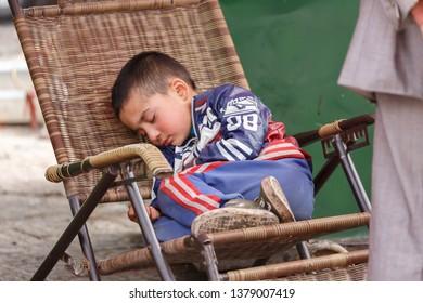 KASHGAR, XINJIANG / CHINA - October 1, 2017: Uyghur boy sleeping on chair at a market in Kashgar.