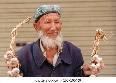 KASHGAR, XINJIANG / CHINA - October 1, 2017: Elderly man with beard showing garlic at a market in Kashgar. The man has a smile on his face and wears a traditonal doppa hat. Uyghur minority in China.