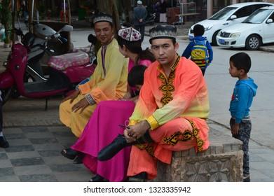 Kashgar, Xinjiang, China - October 19 2018: Kashgar, Xinjiang, China - October 19 2018: Local people  in Kashgar at the main road waiting to show the traditional dancing performance on the main stage