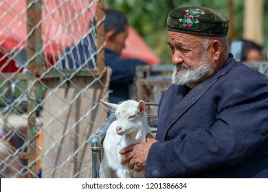 Kashgar, Xinjiang, China - September 16, 2018 :    Profile portrit of old Uyghur man with young goat at the Sunday Livestock Bazaar and Market in Kashgar, or Kashi, China.