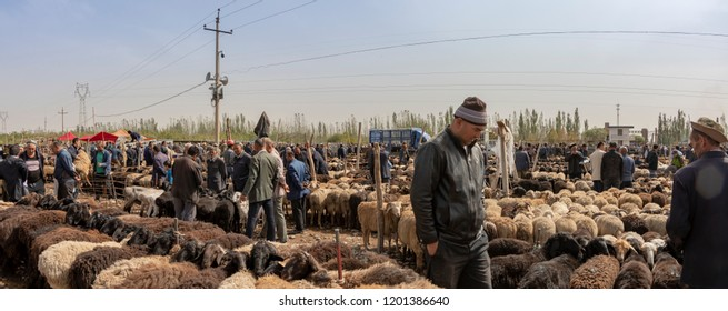Kashgar, Xinjiang, China - September 16, 2018 :    Panorama of Uyghur men haggling over sheep at the Sunday Livestock Bazaar and Market in Kashgar, or Kashi, China.