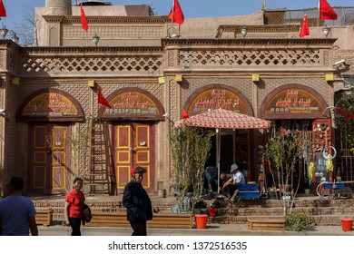 KASHGAR, XINJIANG / CHINA - September 30, 2017: House with traditional Uyghur shops, located in the old city of Kashgar. There are Chinese flags on top of the building due to National holiday.