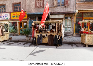 KASHGAR, XINJIANG / CHINA - September 30, 2017: Booth at a market in Kashgar with cloth on display for sale. A huge chinese flag is waving on top of the booth due to Chinese National Holiday.