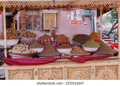 KASHGAR, XINJIANG / CHINA - September 30, 2017: Nuts and raisins on display for sale at a bazaar in Kashgar. The shopkeeper is waiting for customers and is watching the photographer suspiciously.