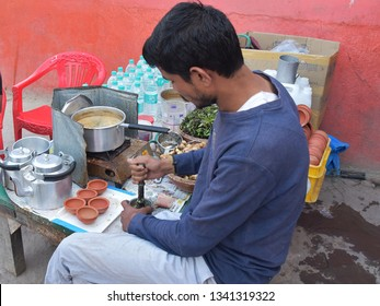 KASHI (VARANASI), UTTAR PRADESH, INDIA, MARCH 01, 2019: Vendor preparing  masala tea, with crushed ginger, balsam leaves and cardamon, on the banks of Assi Ghat. Tea will be served in earthen cups.