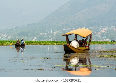 KASHMIR, INDIA - 20th SEPT 2019; Sightseeing over Dal Lake using a shikara - a type of wooden boat. Shikara are of varied sizes and are used for multiple purposes, including transportation of people.