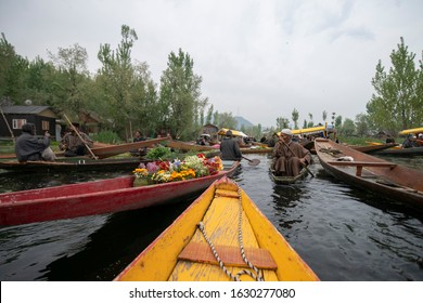 KASHMIR, INDIA - APRIL 16, 2019: Morning view of traditional floating market. Kashmiri men buying and selling vegetables at floating market on Dal Lake. The tourist attractive destination