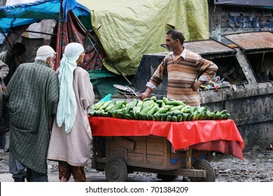 Kashmir, India - August 23, 2017 : unidentified man selling cucumber vegetables and talk with customers at street market as the normal life in Kashmir, India.