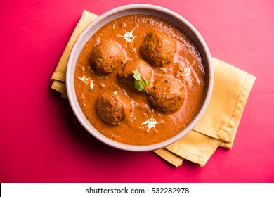 Kashmiri Dum Aloo or spicy Potato Curry, Garnished with Fresh cream and coriander. Served with Rice or Naan/Roti, over colourful/wooden background. Selective focus