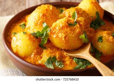 Kashmiri dum aloo: spicy potato closeup on the pan on the table. Horizontal