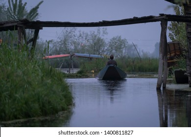 Kashmiri men old wooden boat rowing to floating market on Dal Lake daily early morning is major tourist attractions in Srinagar