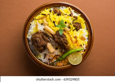 Kashmiri Mutton Gosht Biryani prepared in Basmati Rice served with Yogurt dip over moody background, Selective focus