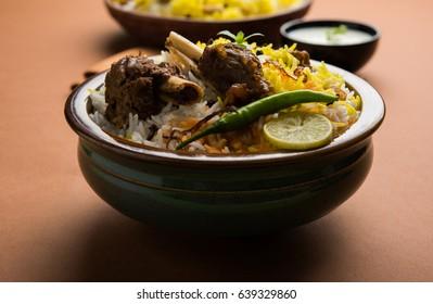 Kashmiri Mutton Gosht Biryani prepared in Basmati Rice served with Yogurt dip over moody background, Selective focus