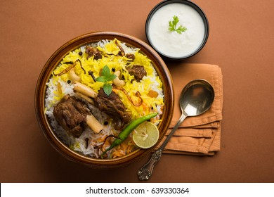 Kashmiri Mutton Gosht or Lamb Biryani prepared in Basmati Rice served with Yogurt dip over moody background, Selective focus
