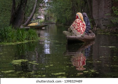 Kashmiri woman Indian rowing wooden boat to floating market on Dal Lake early morning is major tourist attractions in Srinagar