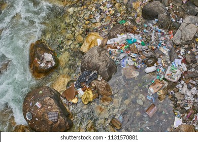 Kasol, Himachal Pradesh / India - 06 27 2018: Garbage in the Parvati river next to Kasol.