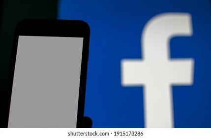 Kassel Germany - February 12,2021:blank smartphone display and blurred Facebook logo background