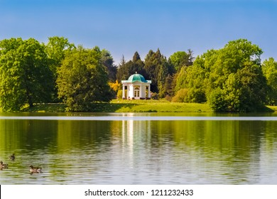 Kassel, Germany - MAY 12, 2008: Beautiful scenery of Swan Island (Schwaneninsel) with its small white temple and ducks swimming on the lake (Aueteich) on a nice sunny day in the Karlsaue park.