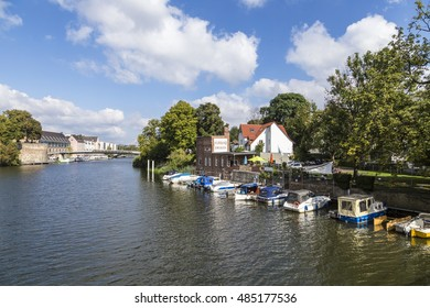 KASSEL, GERMANY -  SEP 18, 2016: skyline of Kassel vith view to Auedamm at river Fulda under blue sky. Boats park at museum Pier Jungborn.
