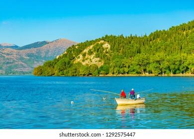 KASTORIA, GREECE, SEPTEMBER 10, 2017: fisherman in a boat on lake orestiada/kastoria in Greece