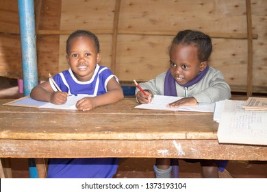 Kasubi, Makerere, Kampala, Uganda - April 10 2019: Unidentified young children preparing for exams in Makerere West Valley Primary school near the slums, being supported by a teacher to finish nursery